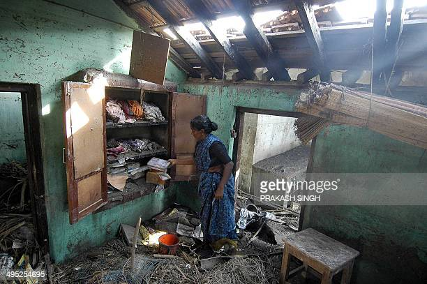 An Indian woman cries as she sifts through her belongings in her devastated house in Akarapatti fishers colony on the seashore near Nagapattinam port...