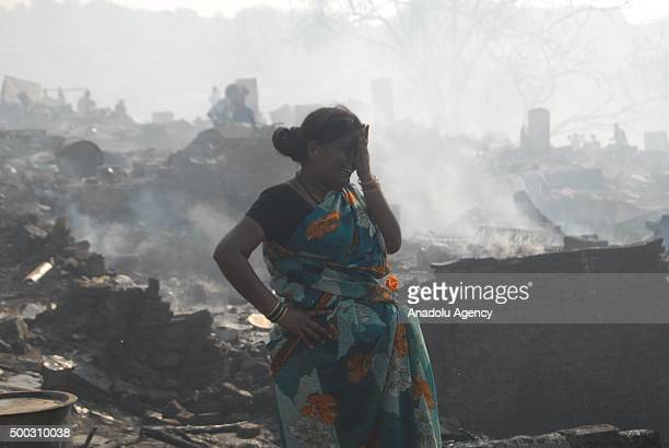 An Indian woman cries as she tries to collect her belongings from the charred remains following a fire at a slum in the east of Kandivali an area in...