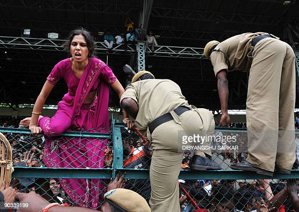 An Indian woman crosses a boundary fence as police officers attempt to control a crowd paying their final tributes to deceased Indian Chief Minister...