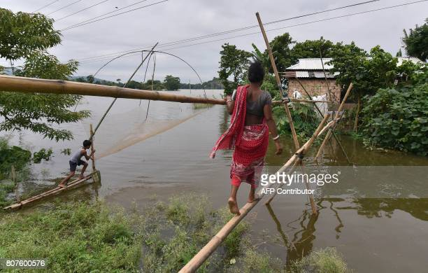 An Indian woman crosses over flood waters along a bamboo bridge in Balimukh Ashigarh village in Morigoan district in India's northeastern state of...