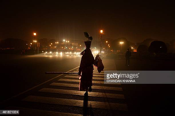 An Indian woman crosses the road in New Delhi on January 20 2015 India is part of a global trend that is advancing towards an increasing urbanisation...