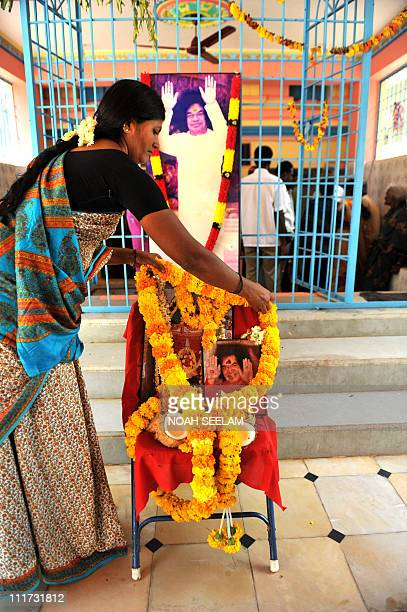 An Indian woman devotee offers prayers to the local deity Goddess Satyamma for the speed recovery of Satya Sai Baba inside the temple at Puttaparthi...
