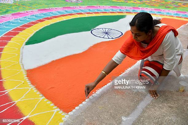 An Indian woman draws a 'rangoli' with the Indian national flag on the eve of the 68th Indian Republic Day celebrations in Bangalore on January 25...