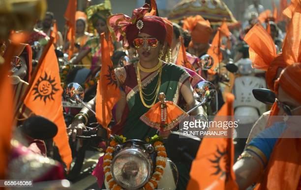An Indian woman dressed in traditional attire drives a motorcycle as she takes part in a procession celebrating 'Gudhi Padwa' or the Maharashtrian...