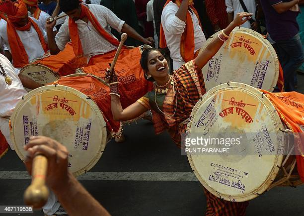 An Indian woman dressed in traditional attire plays a drum during a procession celebrating 'Gudhi Padwa' or the Maharashtrian new year in Mumbai on...