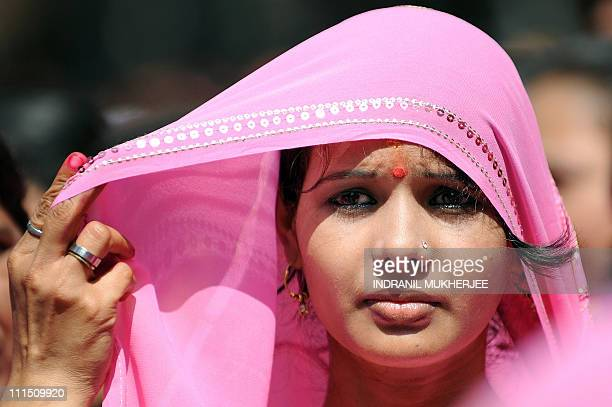 An Indian woman dressed in traditional traditional attire adjusts her saree during a procession to celebrate 'Gudi Padwa' or the Maharashtrian new...