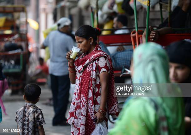 An Indian woman drinks sugar cane juice on a hot summer day in the old quarters of New Delhi on April 26 2018
