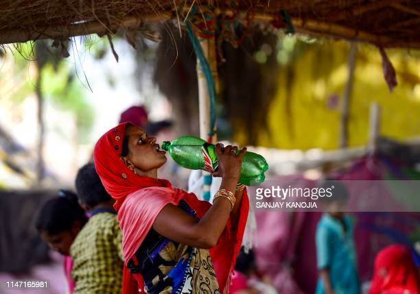 An Indian woman drinks water from a bottle on a hot summer afternoon in Allahabad on May 31, 2019.