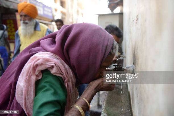 An Indian woman drinks water from a tap outside a temple in Amritsar on March 22 2018 World Water Day is observed on March 22 and focuses on the...