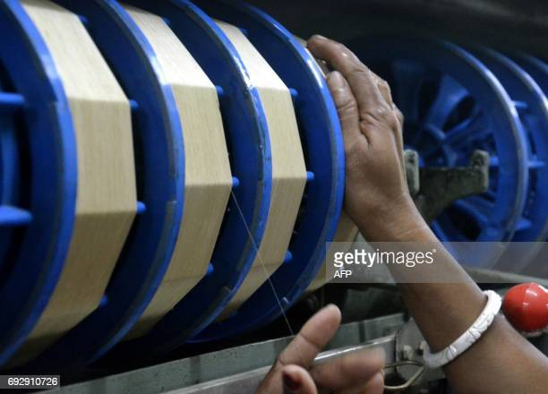 An Indian woman examining a thread of silk on a reel at a silk factory in Dharmanagar in India's northeastern state of Tripura on June 6 2017 The...