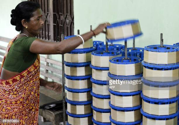 An Indian woman handles a reel of silk at a factory in Dharmanagar in India's northeastern state of Tripura on June 6 2017 The silkworms are grown in...