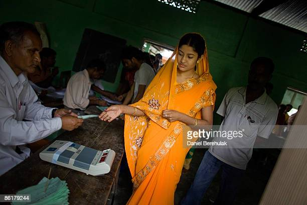 An Indian woman hands in her voting slip before casting her vote at a polling station on April 23 2009 in the Muslim dominated town of Mukalmua near...