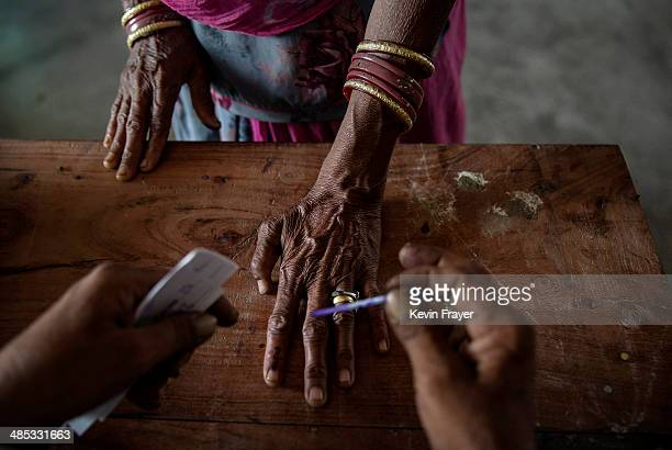 An Indian woman has her finger inked by an elections worker before voting at a polling station on April 17, 2014 in the Jodhpur District in the...