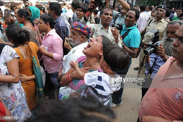 An Indian woman holding a child reacts as her convicted husband is taken away in a police vehicle from inside the Trial Court compound in Ahmedabad...