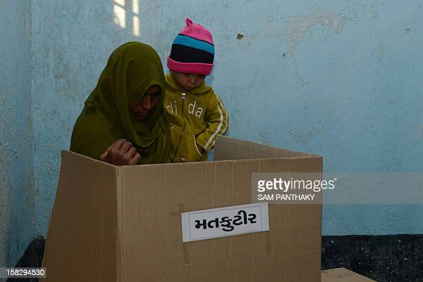 An Indian woman holdS an infant as she casts her vote in the state assembly elections at Sanand some 30 kms from Ahmedabad on December 13 2012 The...