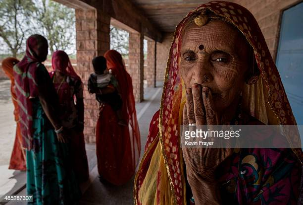 An Indian woman holds her ink stained finger to her face as she leaves after voting at a polling station on April 17 2014 in the Jodhpur District in...
