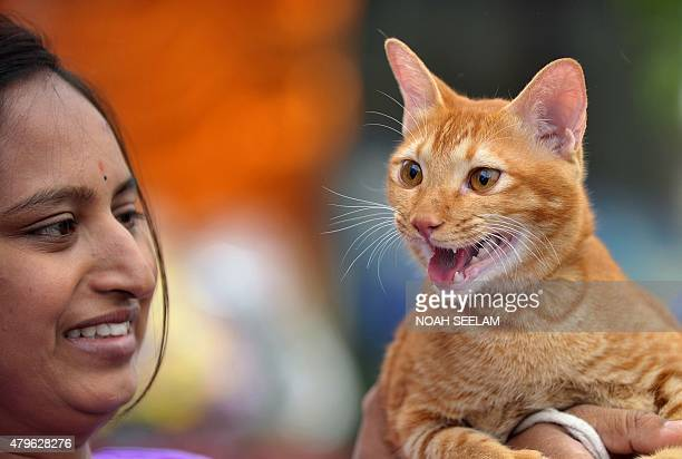 An Indian woman holds her pet cat at the free vaccination camp at the Government Super Speciality Veterinary Hospital on the occasion of World...