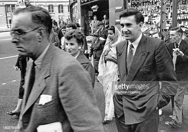 An Indian woman in a sari among a group of pedestrians crossing a London street October 1955 Original publication Picture Post 8572 Indians In London...