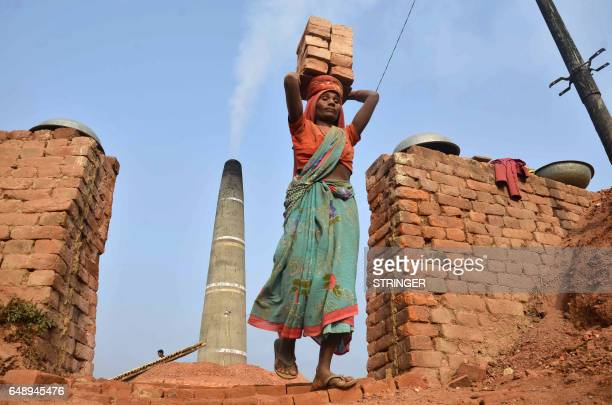 TOPSHOT An Indian woman labourer carries bricks at a factory in Radhapur on the outskirts of Dharmanagar in the north eastern state of Tripura on...
