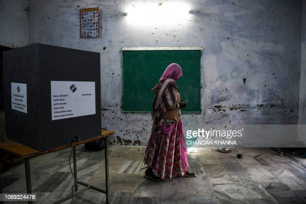 TOPSHOT An Indian woman leaves the poling booth after casting her vote at a local polling station during Rajasthan's Legislative Assembly election in...