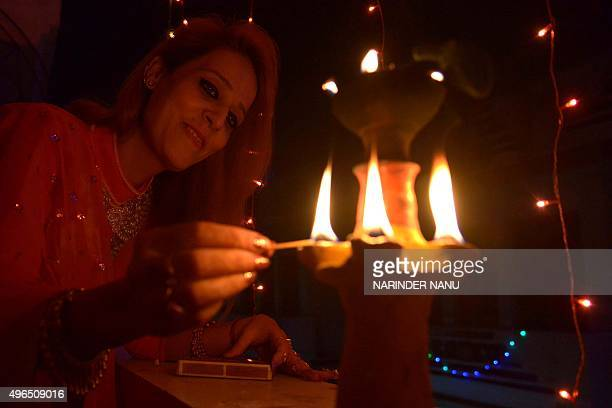 An Indian woman lights an earthen lamp in Amritsar on November 10 2015 on the eve of the Indian festival of Diwali Diwali the Festival of Lights...