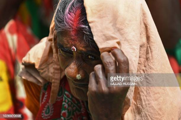 TOPSHOT An Indian woman looks on at a protest rally called by the Centre of Indian Trade Unions affiliated with the Communist Party of India Marxist...