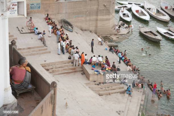 An indian woman on a balcony wtach the people siting down the stairs i front of the Gange river and having a bath in the Gange river. There are some...