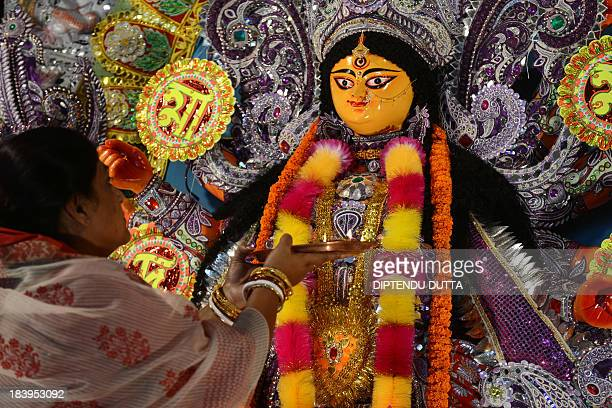 An Indian woman performs Aarti in front of a statue of the Hindu goddess Durga inside a worship place on October 10 2013 The event commemorates the...