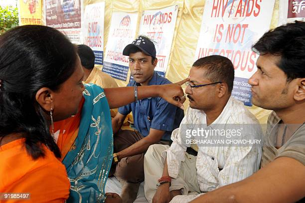An Indian woman places 'tilak' a religious holy mark of sandalwood paste on the forehead of an HIVpositive man in observance of 'Bhai Phota' festival...