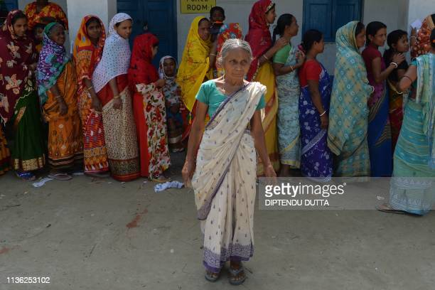 An Indian woman poses for a picture as she queue to caste his vote during India's general election at a polling station in Cooch Behar district, in...