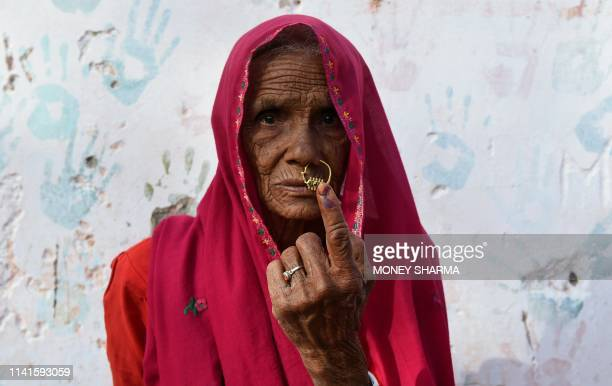 TOPSHOT An Indian woman poses for a picture as she shows her inkmarked finger after casting her vote during India's general election in village...