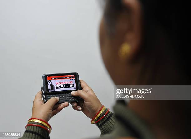 An Indian woman poses with a mobile phone to illustrate a new application alert for women in New Delhi on December 20 2011 A smartphone app launched...