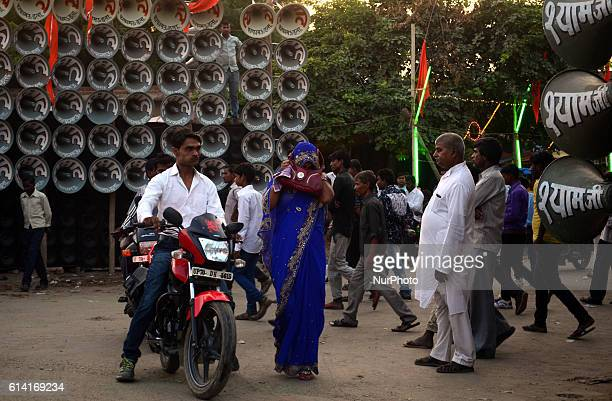 An Indian woman protects her ears as she walks next to loud music loudspeaker competition during a local fair in soraon villagesome 23 kms from...