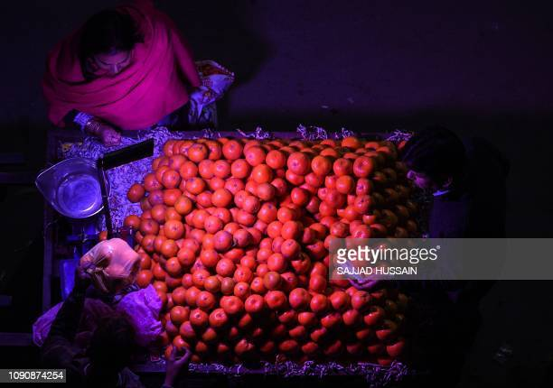 TOPSHOT An Indian woman purchases oranges from a roadside vendor in New Delhi on January 29 2019