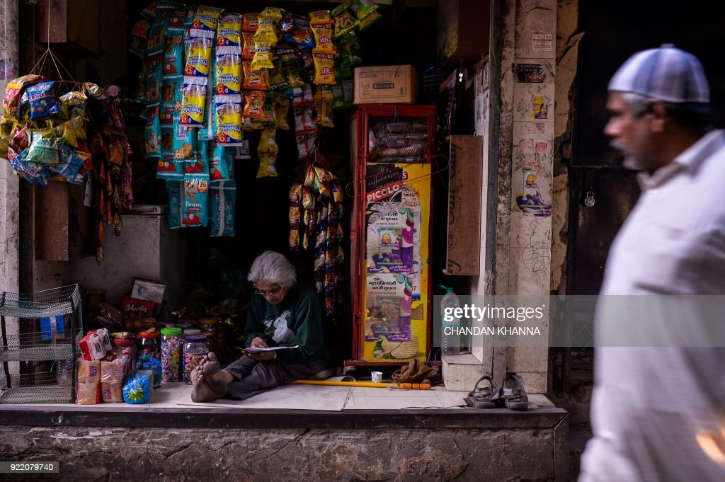 An Indian woman reads a book as she sits inside her shop in the old quarters of New Delhi on February 21, 2018. /