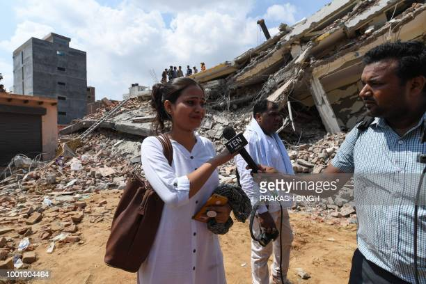 An Indian woman related to a family thought to be inside a residential building that was crushed by a building that collapsed talks to a TV...