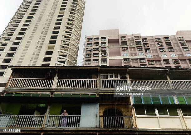 An Indian woman residing in a chawl traditional old tenement for the working class stands on her house balcony as a new highrise tower and a building...