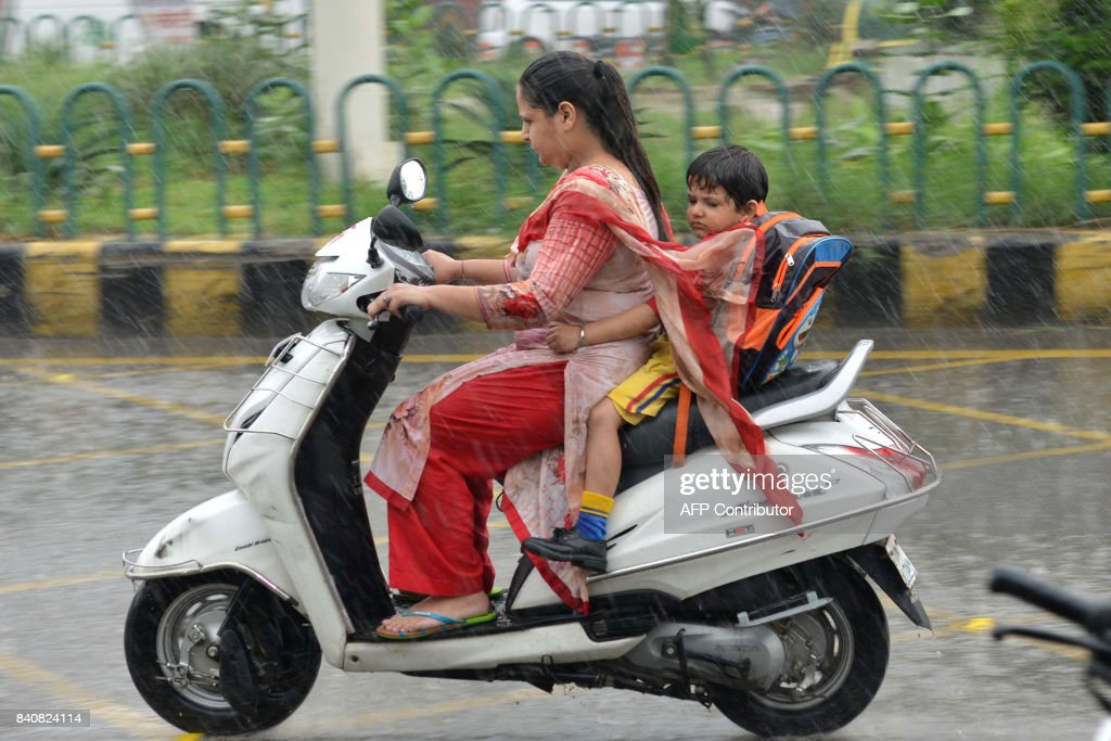 An Indian woman rides a bike with a boy during heavy rains in Amritsar on August 30 2017 / AFP PHOTO / NARINDER NANU