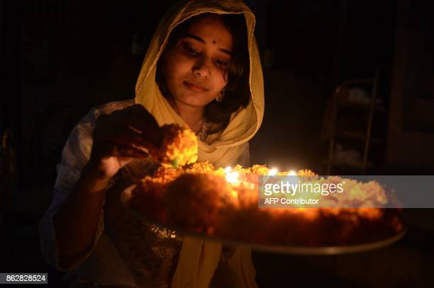 An Indian woman Rishitha places earthen lamps or 'diyas' at her home on the eve of Diwali Festival in Hyderabad on October 18 2017 Diwali the Hindu...