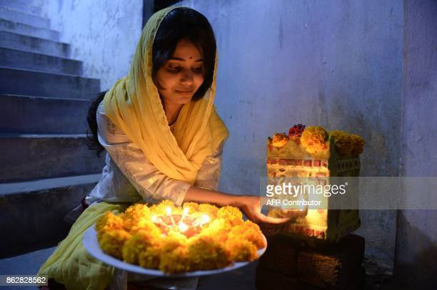TOPSHOT An Indian woman Rishitha places earthen lamps or 'diyas' at her home on the eve of Diwali Festival in Hyderabad on October 18 2017 Diwali the...