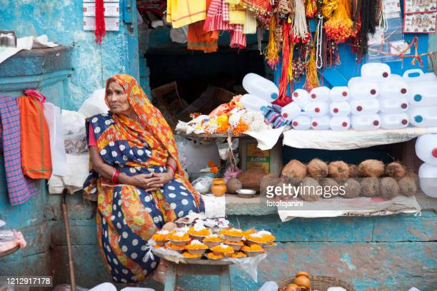 an indian woman selling out his shop varanasi - fotofojanini foto e immagini stock
