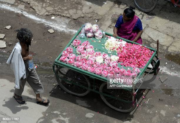 An Indian woman sells rose petals on a street in Hyderabad on June 23 2017 / AFP PHOTO / Noah SEELAM