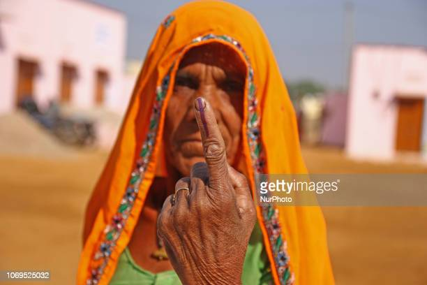 An Indian woman shows her indelible ink marked after casting vote for the state Assembly elections outside the polling station at Raisar Village of...