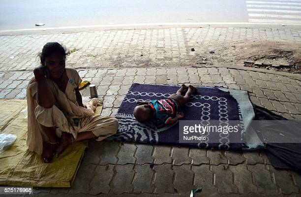 An indian woman sit near her child as her child sleeps in footpathin Allahabad on July 52015 A new report by UNICEF warns that economic growth is...