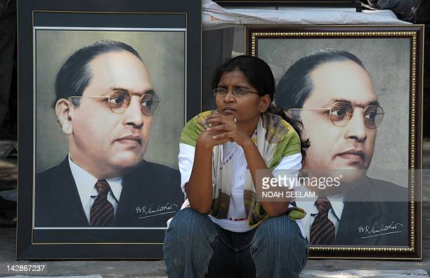 An Indian woman sits infront of portraits of Bhimrao Ramji Ambedkar during 122nd birth anniversary celebrations for Ambedkar in Hyderabad on April 14...