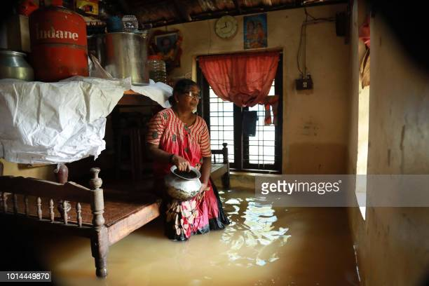 TOPSHOT An Indian woman sits inside her houses immersed in flood waters in Ernakulam district of Kochi in the Indian state of Kerala on August 10...