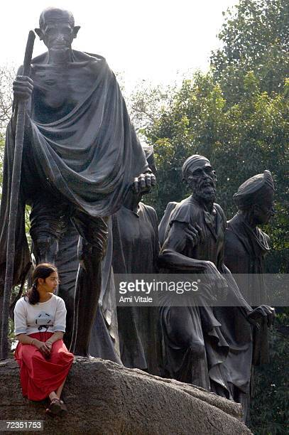 An Indian woman sits on a statue of Mahatma Gandhi before a memorial by the All India Terrorist Front for slain American journalist Daniel Pearl...