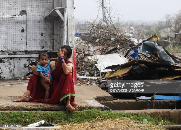 TOPSHOT An Indian woman sits with her child next to stormdamaged buildings in Puri in the eastern Indian state of Odisha on May 4 after Cyclone Fani...