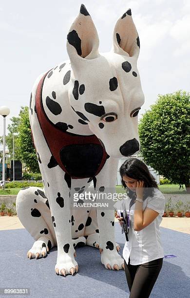 An Indian woman speaks on a cellular telephone as she walks past a sculpture by Ved Prakash Gupat's work 'Dog democracy threshold' a 117x135x84 inch...