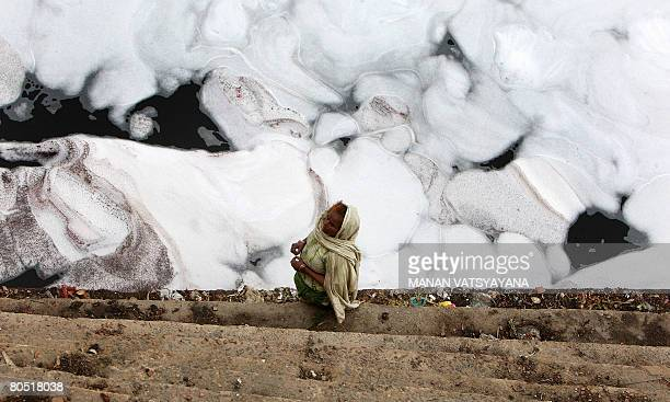 An Indian woman stands on the banks of the polluted waters of the Yamuna River in New Delhi on April 4 2008 The national capital is a major culprit...